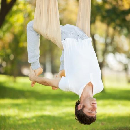 Anti-gravity Yoga, man doing yoga exercises in the park Stock Photo