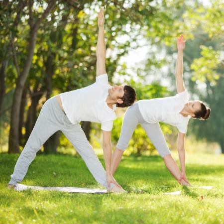 Paar-Yoga, Mann und Frau, die Yoga-Übungen im Park Standard-Bild - 24679416