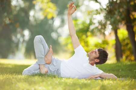 Man doing yoga exercises in the park photo