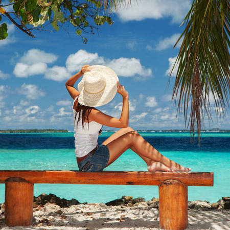 siting: Fashion woman siting on a bench at the beach Stock Photo