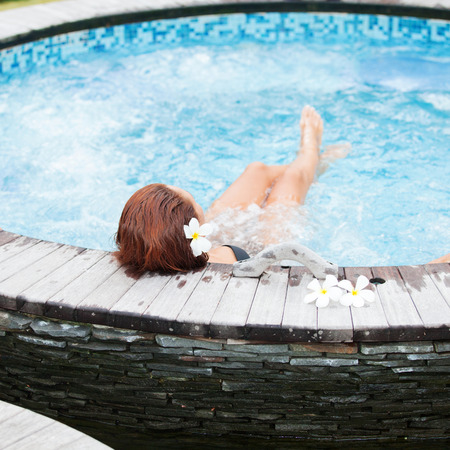 Beautiful woman relaxing in jacuzzi at spa centre photo