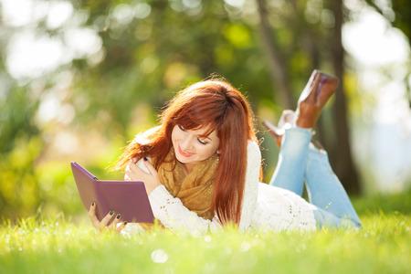 mujer leyendo libro: Mujer bonita joven con la tableta en el parque