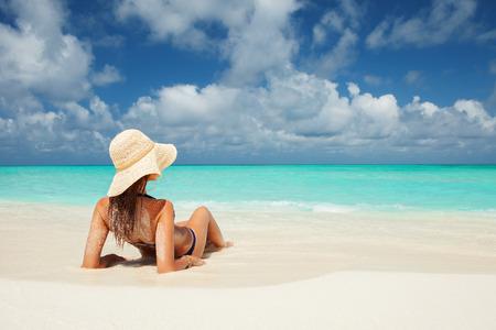 若い女性のファッションはビーチでリラックス