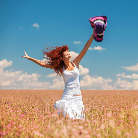 Cute woman running in the field with flowers photo