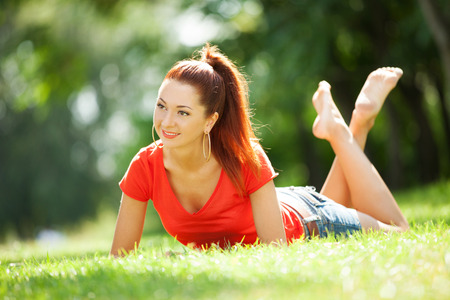 Young pretty woman relaxing in the park photo