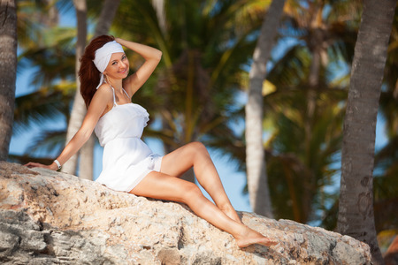 Fashion woman relaxing under palm trees photo