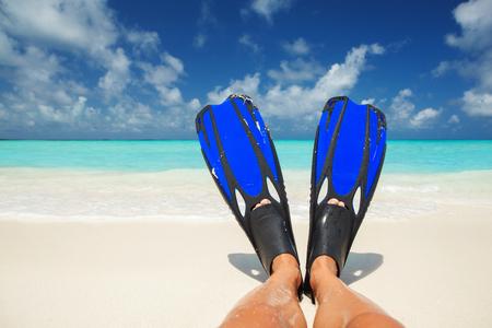 flippers: Buceador se relaja en la playa. Piernas bronceadas en aletas azules en la arena blanca, azul cielo nublado y el mar de fondo de cristal. estilo de vida feliz isla. Vacaciones en el Paraíso. Viaje a la playa tropical