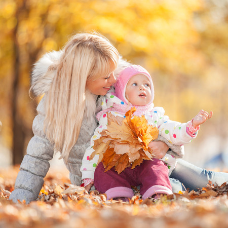 Mother and daughter walking in the autumn park. Beauty nature scene with colorful foliage background, yellow trees and leaves at fall season. Autumn outdoor lifestyle. Happy smiling family relax on fall leaves photo