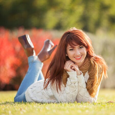 woman smiling: Young woman walking in the park. Beauty nature scene with colorful background, trees and leaves at fall season. Autumn outdoor lifestyle. Happy smiling woman relax on green grass Stock Photo
