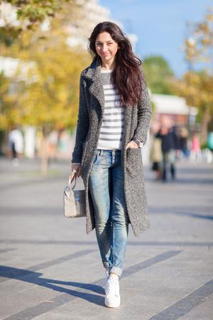 Mujer con estilo hermosa en tejanos, zapatos de moda y acogedor abrigo de trinchera paseo en parque de la caída de la ciudad. Otoño estilo de vida al aire libre. La mujer feliz goza de la caída. estilo de la calle, equipo de moda. Retrato de la caída de la mujer