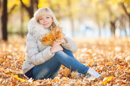 Young pretty woman relaxing in the autumn park photo