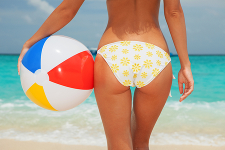 Summer beach concept. Sexy woman with ball on the blue sea and cloudy sky background, sandy woman buttocks on the beach background. Tanned summer woman body
