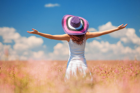 Happy woman enjoing the life in the field with flowers. Nature beauty, blue cloudy sky and colorful field with flowers. Outdoor lifestyle. Freedom concept. Woman in summer field Stock Photo