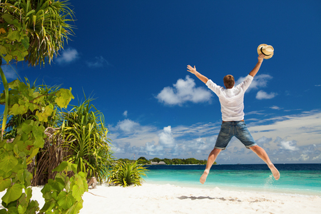 Happy man jumping on the tropical beach. White sand, blue cloudy sky and crystal sea of tropical beach. Vacation at Paradise. Happy island lifestyle. Ocean beach relax, travel to Maldives islands photo