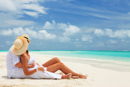 Happy honeymoon vacation at Paradise. Couple relax on the white sand of beach. Happy sea lifestyle. Young family, man and woman rest on the beach of ocean. Couple in love travel to island. Love travel photo