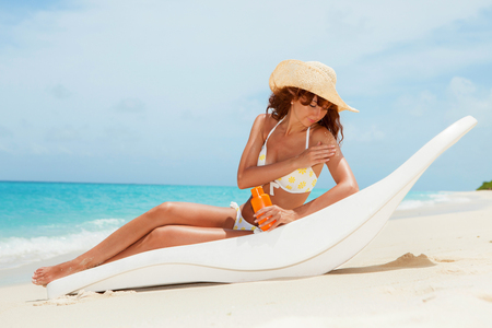 Young tanned woman in bikini sit at chaise-longue and apply sun-protection cream to her skin on the beach. Happy woman vacation at Paradise. Relax on the beach. Sea lifestyle. Protection of skin on the beach at summertime.