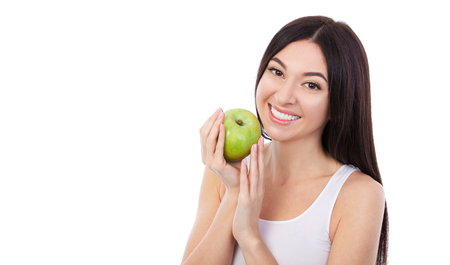Cute woman with beautiful snow-white smile holding green apple. Healthy lifestyle and nutrition, dieting, weight loss, cosmetology, dental care and healthy teeth consept. Close up portrait of beautifu 写真素材