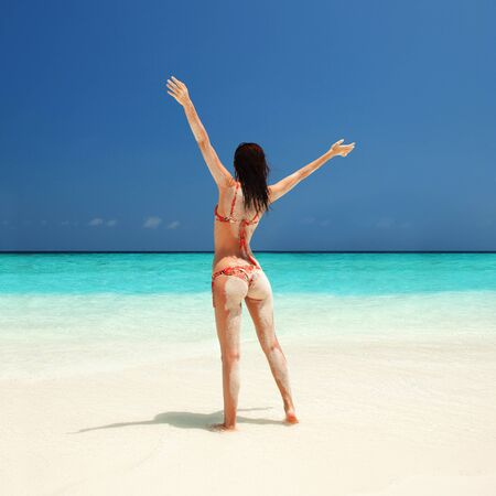 Sandy woman in bikini relax on the beach. Summer lifestyle concept. Tanned body on blue sea and sky background. Beautiful woman enjoy her vacation Standard-Bild