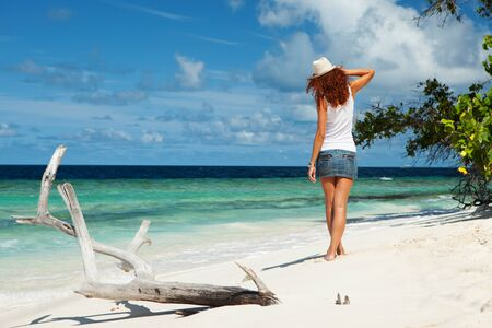 Fashion woman walking on the beach. Happy island lifestyle. White sand, blue cloudy sky and crystal sea of tropical beach. Vacation at Paradise. Ocean beach relax, travel to Maldives islands