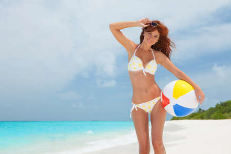 Young pretty woman with ball on the beach background. Happy lifestyle. White sand, blue sky and crystal sea of tropical beach. Vacation at Paradise. Ocean beach relax, travel to islands