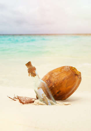 A letter in a bottle and coconut on the beach. Island lifestyle. White sand, crystal-blue sea of tropical beach. Ocean beach relax, travel to islands