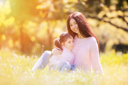Happy mother and daughter in the autumn park. Beauty nature scene with family outdoor lifestyle. Happy family resting together on grass, having fun outdoor. Happiness and harmony in family life