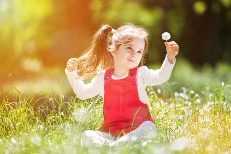 Cute little girl play in the park with flowers. Beauty nature scene with colorful background at summer or spring season. Family outdoor lifestyle. Happy girl relax on green grass Standard-Bild