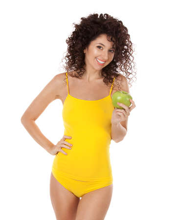 Cute curly woman with beautiful snow-white smile in yellow lingerie holding green apple. Healthy lifestyle and nutrition, dieting, weight loss, cosmetology, dental care and healthy teeth conсept Zdjęcie Seryjne