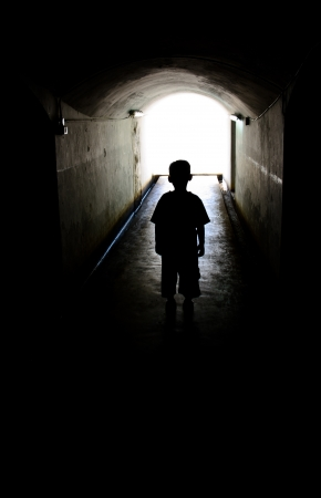 young boy in long tunnel walkway with the white light at the end
