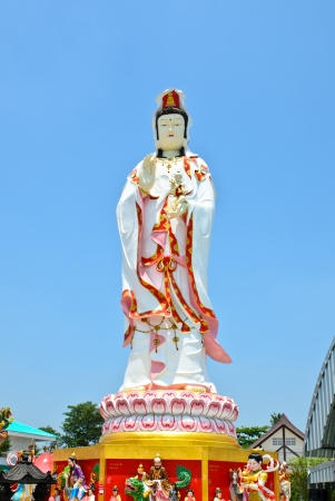 The Guan Yin Buddha Statue Standing on Lotus Flower Isolated on blue sky Background photo