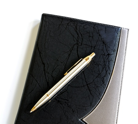 pen lying on a notebook photo