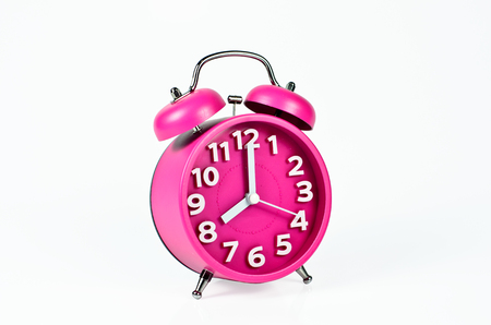 Retro pink alarm clock isolated on white photo