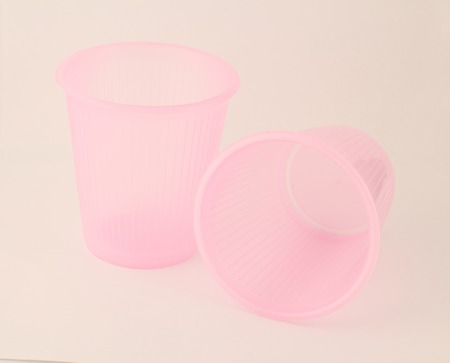 Two pink plastic cup isolated on white background photo