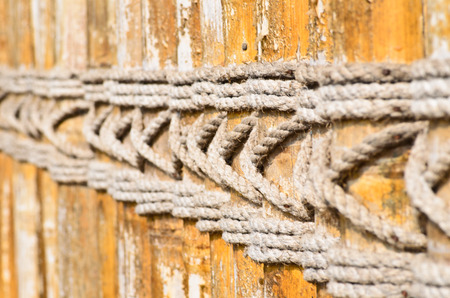 Wooden fence with braided ropes Stock Photo
