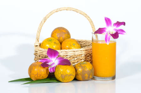 Glass of orange juice with oranges in basket