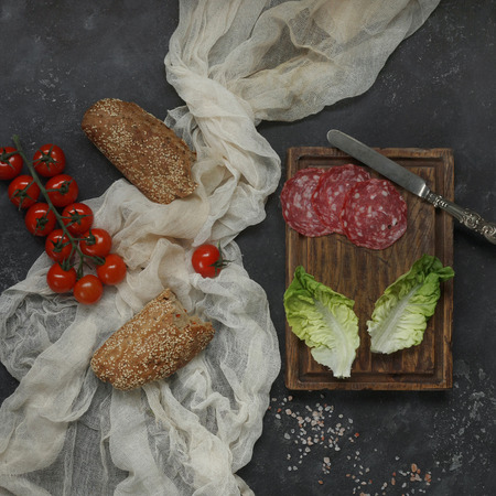 Ingredients for sandwich, Sausage on wooden board with lettuce and vintage knife, bread with tomatoes and textile napkin on black stone background, Top View, Horizontal,  Selected focus