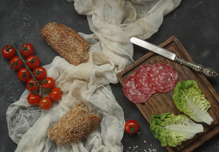 selected: Ingredients for sandwich, Sausage on wooden board with lettuce and vintage knife, bread with tomatoes and textile napkin on black stone background, Top View, Horizontal,  Selected focus