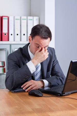 Business-Mann mit Kopfschmerzen, erschöpft oder traurig Standard-Bild