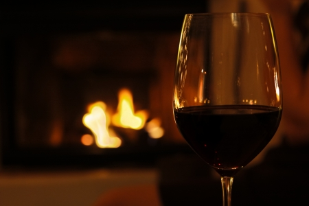 glass of red wine at cozy fireplace in winter photo