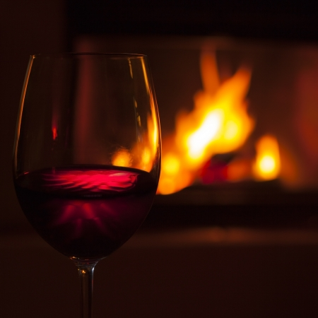 glass of red wine at cozy fireplace in winter Banque d'images