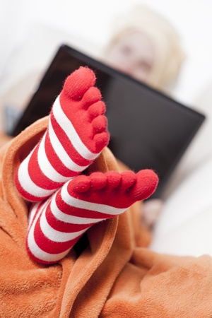 red bathrobe: woman in warm toe socks and blanket at home