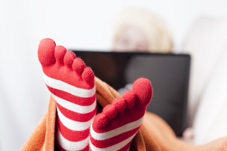 woman in warm toe socks and blanket at home
