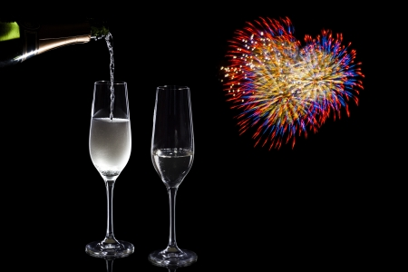 pouring champaign in front of heart shaped fireworks photo