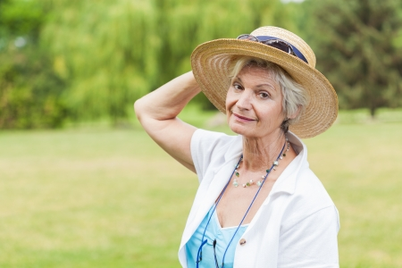 best ager women posing outdoors with hat photo