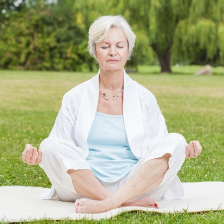 meditating woman: best ager women practising yoga and tai chi outdoors Stock Photo
