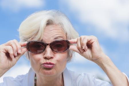 Best Ager Frauen posiert mit Sonnenbrille im Freien vor blauem Himmel