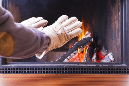 warming hands at cozy warm fireplace in winter photo