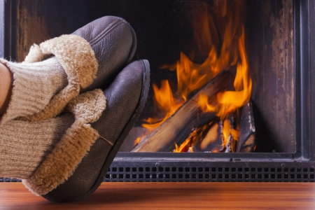 relaxing in comfy rustic slippers at cozy warm fireplace in winter Standard-Bild