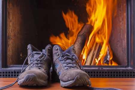 drying hiking shoes at cozy warm fireplace in winter