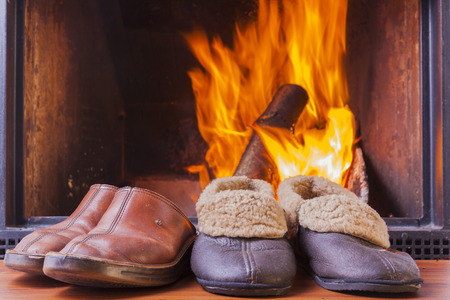 comfy rustic slippers at cozy warm fireplace in winter photo